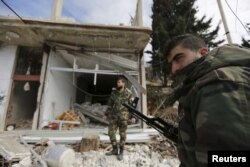 FILE - Forces loyal to Syria's President Bashar al-Assad stand in front of damaged shops in the town of Rabiya after they recaptured the rebel-held town in coastal Latakia province, Syria, Jan. 27, 2016.