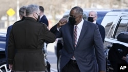 Defense Secretary Lloyd Austin, right, greets Chairman of the Joint Chiefs of Staff Mark Milley as he arrive at the Pentagon, Friday, Jan. 22, 2021, in Washington. (AP Photo/Alex Brandon)