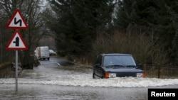 Mobil melalui jalan yang banjir dekat Jembatan Cally, Skotlandia.