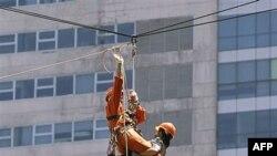Nhân viên cứu nạn đang thực tập đưa nạn nhân từ trên một ngôi nhà cao tầng xuống