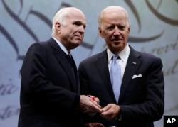 FILE - Sen. John McCain, R-Ariz., receives the Liberty Medal from former Vice President Joe Biden, chairman of the National Constitution Center's Board of Trustees, in Philadelphia, Oct. 16, 2017.