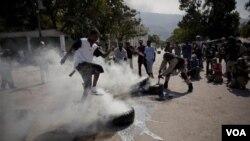 Un policía y un transeúnte intentan apagar el fuego en unos neumáticos iniciado por los manifestantes.
