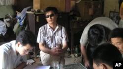 ນາຍ Chen Guangcheng (ກາງ) ນັກເຄຶ່ອນໄຫວຕາບອດ ແລະເພື່ອນນັກເຄຶ່ອນໄຫວດ້ວຍກັນ ທີ່ໝູ່ບ້ານແຫ່ງນຶ່ງ ໃນຈີນ