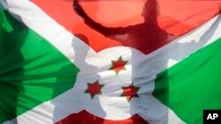 Des silhouettes derrière le drapeau national du Burundi, le 9 juin 2015.