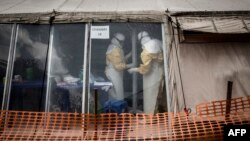"""FILE - Health workers are seen inside the """"red zone"""" of an Ebola treatment center, which was attacked in the early hours of March 9, 2019 in Butembo, DRC."""