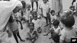 FILE - In this Oct. 25, 1979, photo, Mother Teresa (L) talks with and blesses orphans at her Sishu Bhavan (Children's Home) in Calcutta (now Kolkata), India.