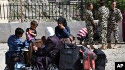 Des réfugiés syriens attendent près de la frontière entre le Liban et la Syrie pour être rapatriés, le 18 avril 2018