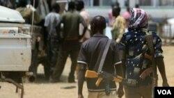 Beberapa pria bersenjata berjalan di kota minyak, Abyei di Sudan Selatan (foto: April 2011).