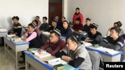 """新疆政府為一小批外國記者組織了對烏魯木齊一個""""再教育營""""的參觀,看維吾爾穆斯林學生上課。(2019年1月3日)"""