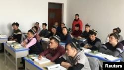 """新疆政府为一小批外国记者组织了对乌鲁木齐一个""""再教育营""""的参观.维吾尔穆斯林学生正在上课。(2019年1月3日)"""