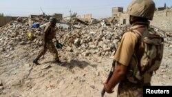 Binh sĩ Pakistan đứng gần đống đổ nát của một ngôi nhà bị phá hủy trong một cuộc phản công chống Taliban.