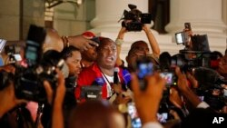 South African Economic Freedom Fighters leader Julius Malema, center, speaks after he and other members leave parliament's opening session in Cape Town, South Africa, Feb. 12, 2015.