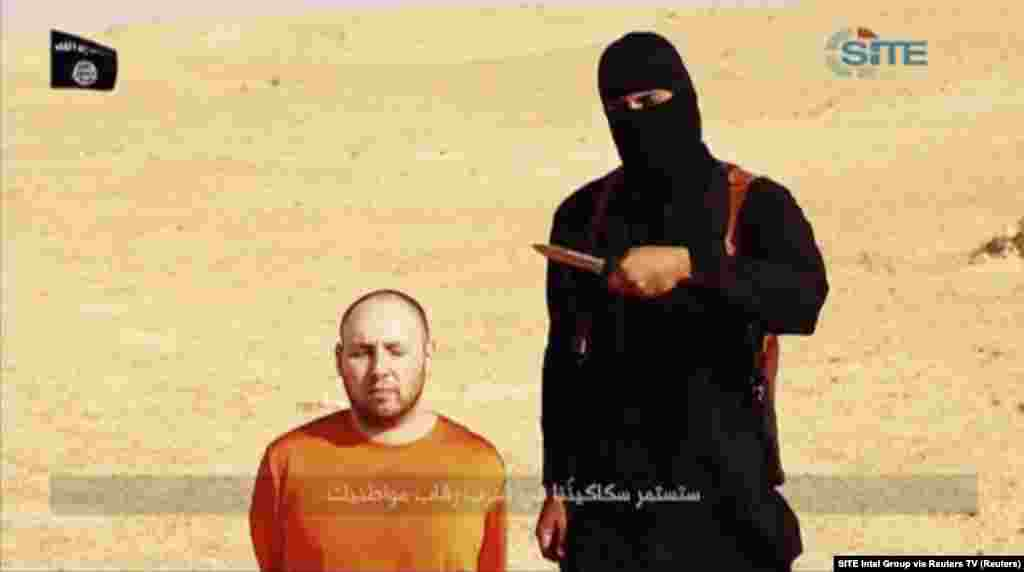 A masked, black-clad militant, identified by The Washington Post newspaper as a Briton named Mohammed Emwazi, stands next to a man purported to be Steven Sotloff in this still image from a video obtained from SITE Intel Group website, Feb. 26, 2015.