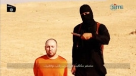 FILE - A masked, black-clad militant, identified by The Washington Post newspaper as a Briton named Mohammed Emwazi, stands next to a man purported to be Steven Sotloff in this still image from a video obtained from SITE Intel Group website, Feb. 26, 2015.