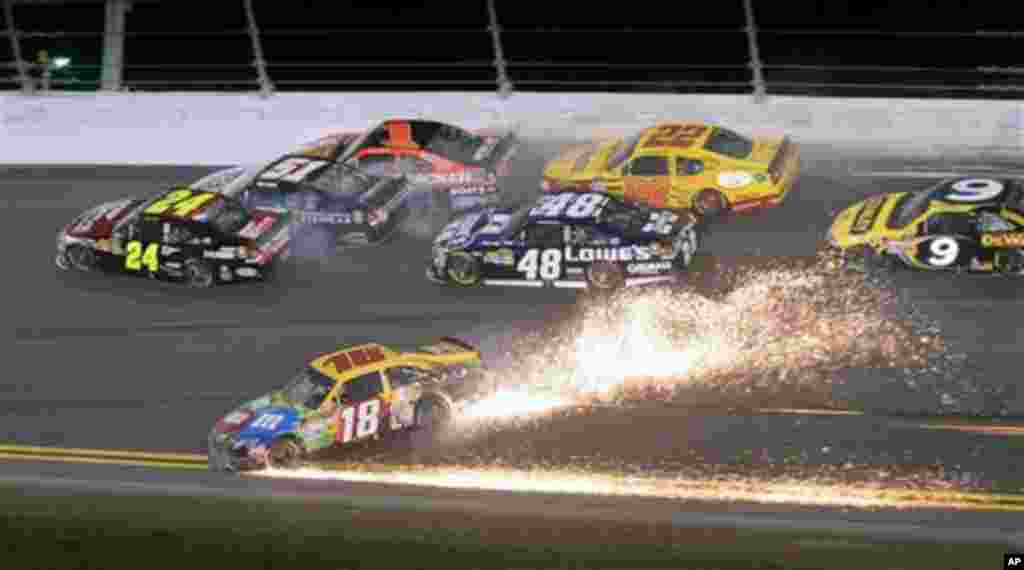 Kyle Busch (18) slides sideways to avoid a wreck as Jeff Gordon (24) heads to the wall before his car slid on its side and then rolled, during the NASCAR Budweiser Shootout auto race at Daytona International Speedway, Saturday, Feb. 18, 2012, in Daytona B