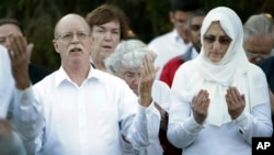 Ed and Paula Kassig, in foreground, pray at a vigil for son Abdul-Rahman Kassig at Butler University in Indianapolis, Indiana, on Oct. 8, 2014.
