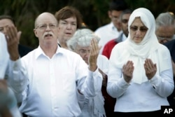FILE - Ed and Paula Kassig, in foreground, pray at a vigil for son Abdul-Rahman Kassig at Butler University in Indianapolis, Indiana, Oct. 8, 2014.