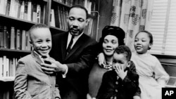 In this March 17, 1963, file photo, Dr. Martin Luther King Jr. and his wife, Coretta Scott King, sit with three of their four children in their Atlanta, Ga., home. From left are: Martin Luther King III, 5, Dexter Scott, 2, and Yolanda Denise, 7.