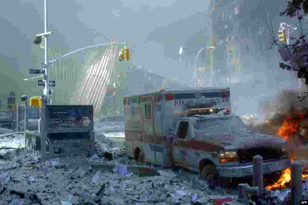 (FILE) An ambulance, covered with debris, is on fire after the collapse of the first World Trade Center Tower 11 September, 2001 in New York. Two hijacked passenger planes were crashed against the twin towers causing the collapsed of both buildings. AFP PHOTO Doug KANTER (Photo by DOUG KANTER / AFP)