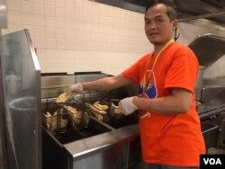 Satriyo Utomo alias Nanang, ketua tim relawan dapur Muktamar IMSA 2019, menggoreng ikan filet di dapur (VOA/Karlina).