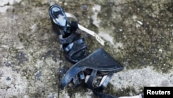 FILE - A woman's shoes lie on a street in Quezaltepeque, July 2, 2013.