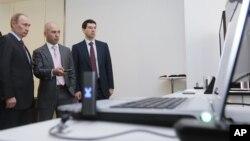 FILE - Russian Prime Minister Vladimir Putin, left, and Russian Communications Minister Igor Shchyogolev, right, with Skartel Director General Denis Sverdlov in 2011. (AP Photo/RIA Novosti)