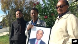 Family members from left, Fobel Tekleab, Fessehatsion Gebreselassie and Abraham Amanios, hold a photo of Isaac Amanios, Dec. 5, 2015.