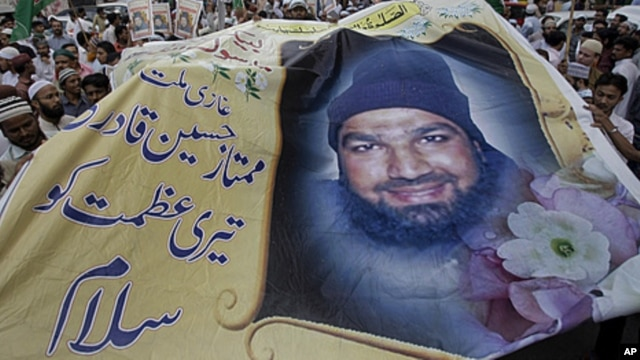 Supporters of religious group Sunni Tehreek hold a huge poster of Mumtaz Qadri, the confessed killer of a liberal Pakistani governor, during a rally to condemn the court decision against Qadri, October 1, 2011 in Karachi.