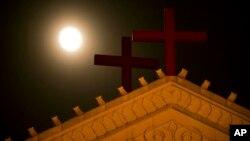 Mặt trăng mọc phía trên thánh giá trên nóc nhà thờ ở Ôn Châu, tỉnh Chiết Giang, miền đông Trung Quốc.