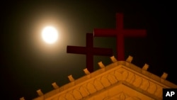 FILE - The moon rises above a pair of crosses on the roof of Holy Trinity Church in Wenzhou in eastern China's Zhejiang Province.