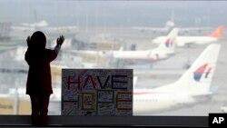 """在吉隆坡国际机场,一个女孩站在签名板旁,签名板上写着""""抱有希望"""""""