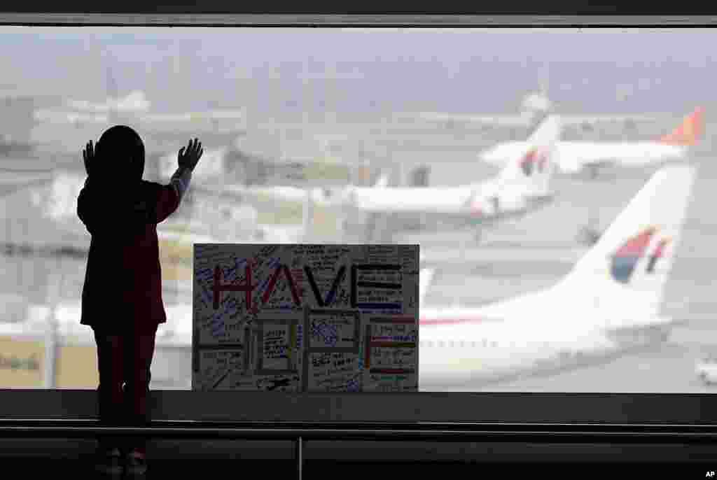 Uma menina observa os aviões da janela da sala de espera do Aeroporto Internacional de Kuala Lumpur em Sepang. Ao lado dela está um cartaz que diz: Tenham Esperança. Malásia, Março 10, 2014.