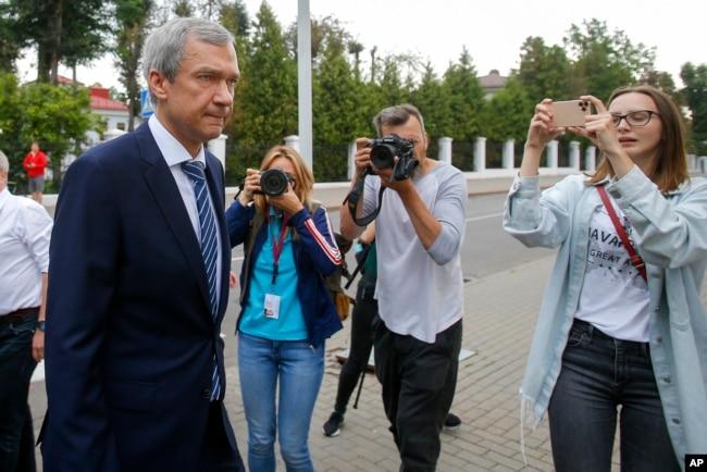 白俄罗斯知名反对派人士拉图什科在明斯克走过一群记者向白俄罗斯调查委员会走去。(2020年8月25日)