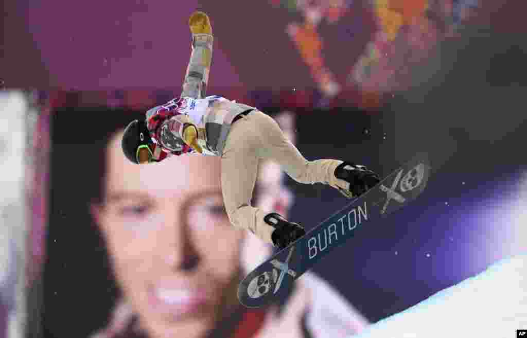 Shaun White of the U.S. performs a jump near a picture of himself during the men's snowboard halfpipe qualification round at the Rosa Khutor Extreme Park, Krasnaya Polyana, Russia, Feb. 11, 2014.