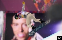Shaun White of the U.S. performs a jump near a picture of himself during the men's snowboard halfpipe qualification round at the 2014 Sochi Winter Olympic Games in Rosa Khutor February 11, 2014. REUTERS/Dylan Martinez (RUSSIA - Tags: SPORT SNOWBOARDING O