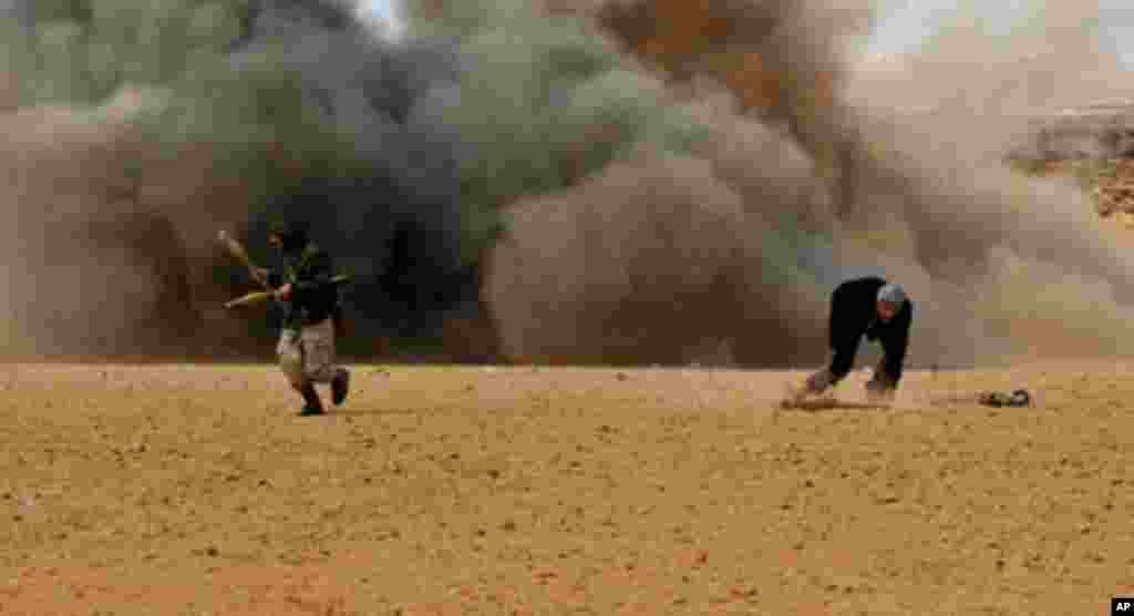 Rebel fighters run for cover as shells explode nearby during a battle with forces loyal to leader Moammar Gadhafi, just a few kilometers outside the oil town of Ras Lanuf, March 9, 2011. (AFP Image)
