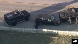 Armored vehicles surround an SUV following a second shootout in which two suspects were killed and a police officer was wounded.