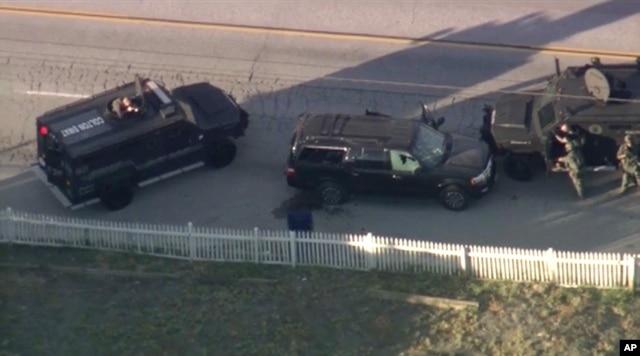 Xe bọc thép của cảnh sát vây quanh chiếc SUV của hai nghi can bị bắn chết trong xe.