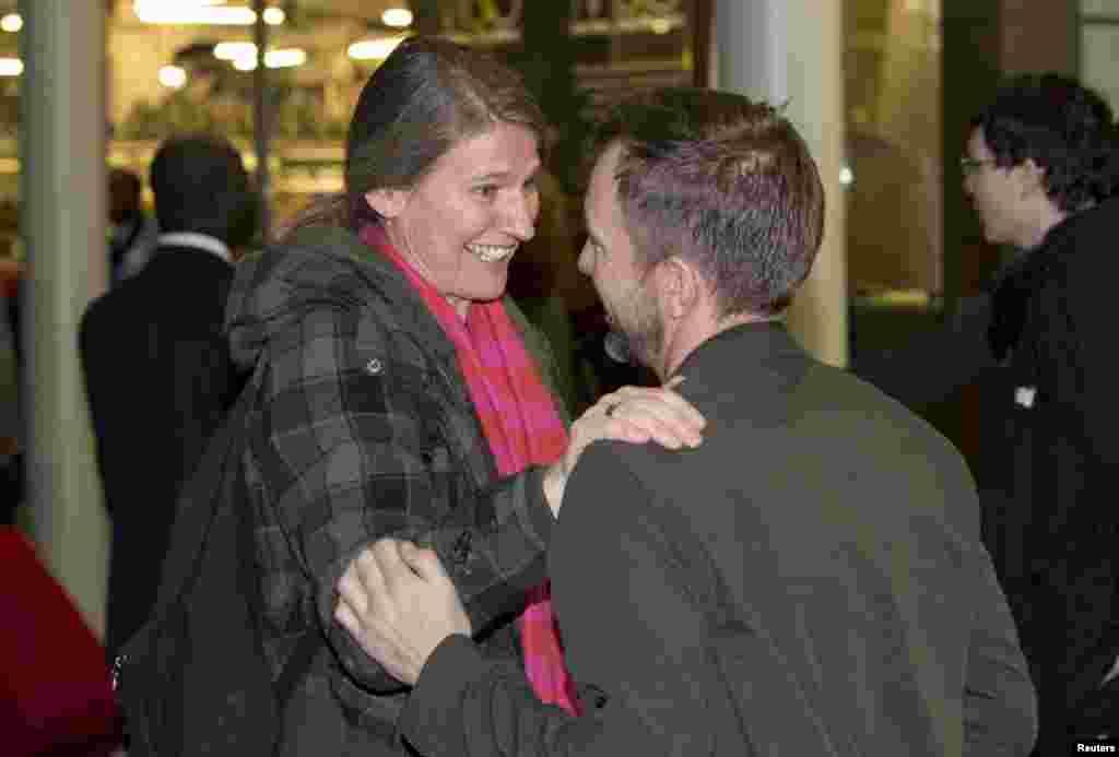 Greenpeace çalışanı Daphane Christelis (solda) Greenpeace aktivisti Phillip Ball'ı karşılarken