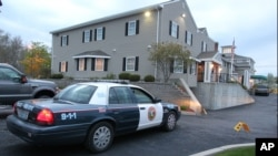 一名麻省北阿特尔伯勒警官守卫在当地的戴尔湖殡仪馆外,该殡仪馆存放着塔梅尔兰的尸体