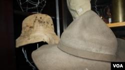 Des centaines de chapeaux et casques de champs de bataille conservés dans un « depot de la guerre » ... y compris le chapeau en arrière-plan qui appartenait à un soldat tué en arrière-plan en conflit dans ce qui est maintenant la Namibie dans les années 1980. (D. Taylor / VOA)