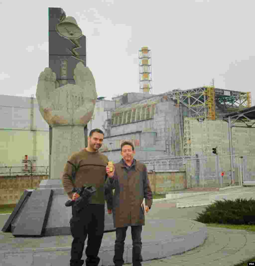 VOA's videographer Arash Arabasadi and correspondent Steve Herman (holding a radiation monitor) in front of the old sarcophagus covering Chernobyl Reactor No. 4. (Arash Arabasadi/VOA)