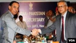 Sekretaris Negara India G.K. Pillay (kiri) berjabat tangan dengan Sekretaris Negara Pakistan Chaudary Qamar Zaman dalam pertemuan di New Delhi, Senin (28/3).
