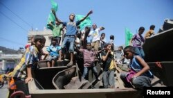 FILE - Palestinian children are seen waving Hamas flags in Khan Younis in the southern Gaza Strip.