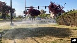 Sprinklers water grass near a street corner Friday, April 9, 2021, in the Summerlin neighborhood of northwest Las Vegas. (AP Photo/Ken Ritter)
