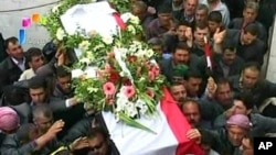 "Syrian state television video footage shows mourners carrying a coffin during the funeral of two members of the security forces after they were allegedly killed by ""armed groups"", in Hama, north of Damascus, on April 10, 2011"