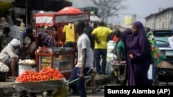FILE - In this Dec. 24, 2020, file photo, people walk in a market in Lagos, Nigeria. Nearly 20 percent of the 4,500 of the people in the study of young people in 15 African countries said they became unemployed because of the pandemic. Some of them turn to selling farm produce or other goods on the street. (AP Photo/Sunday Alamba, File)