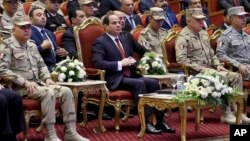 In this photo released by the Egyptian president's office, Egyptian President Abdel Fattah el-Sissi, center, attends a conference commemorating the country's martyrs, in Cairo, March 15, 2018. Up for re-election in less than two weeks, Egypt's president on Thursday took center stage at a televised ceremony declaring his readiness to personally join the battle against militants and decorating soldiers and families of fallen ones.