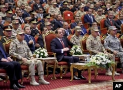 FILE - Egyptian president's office, Egyptian President Abdel Fattah el-Sissi, center, attends a conference commemorating the country's martyrs, in Cairo, March 15, 2018.