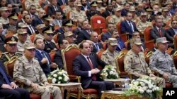 FILE - In this photo released by the Egyptian president's office, Egyptian President Abdel Fattah el-Sissi, center, attends a conference commemorating the country's martyrs, in Cairo, March 15, 2018.
